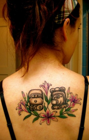Two Mayan symbols surrounded by lillies on girls back