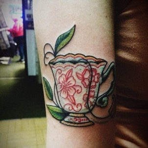Cup of tea with flowers and leaves on girls leg