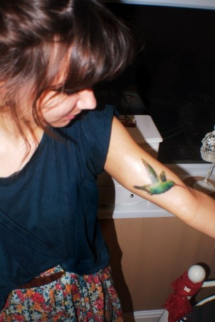 green hummingbird on girls arm