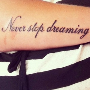 """Never stop dreaming"" quote tattoo on girls arm"