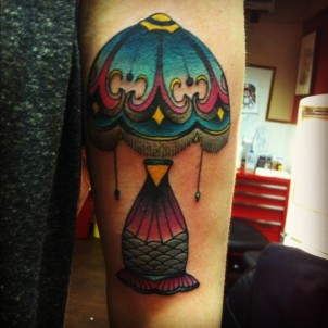 Colorful lamp tattoo on girls arm