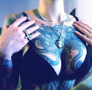 Octopus chest tattoo holding a locket at its center