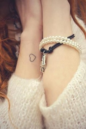 Small and simple heart outline on girls wrist