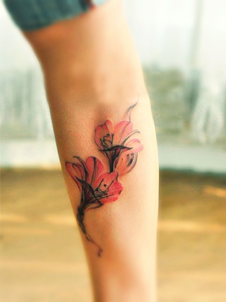 two elegant pink and red alstroemeria flowers on girls leg